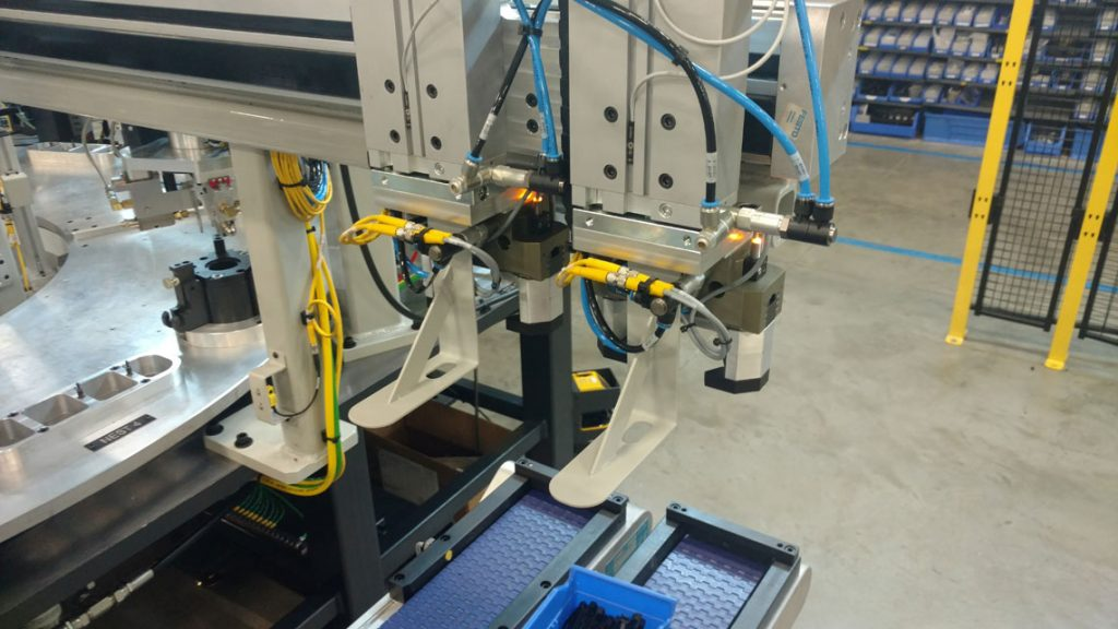 Servo Driven Gripper assembly transfers component pallets to and from main assembly table.
